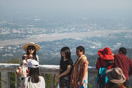Chiang Mai, Thailand - February 7, 2018: Tourists enjoy and taking photos of the city Chiang Mai from the viewing platform of the Wat Phra That Doi Suthep in Thailand.