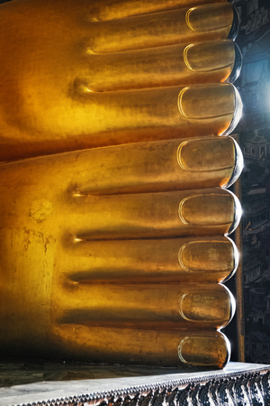 Picture of the golden reclining Buddha statue at the Wat Pho Temple, Bangkok, Thailand. Huge golden feet, asian style Buddha Art