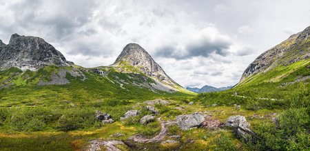 Beautiful mountain scenery near Trollstigen road from Andalsnes to Stranda in Norway, Scandinavia. Panoramic summer landscape with green grass and large picturesque stones in the foreground. 스톡 콘텐츠