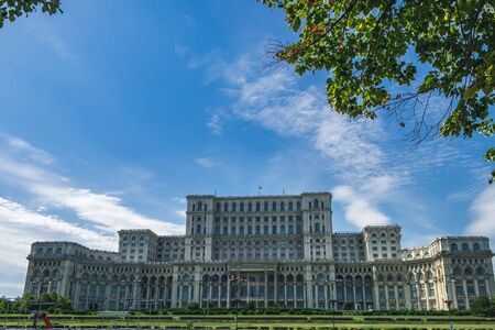 Bucharest, Romania - September 9, 2017: The Palace of Parliament is seen through the autumn foliage of trees and Liberty Avenue, central part of Bucharest, Romania