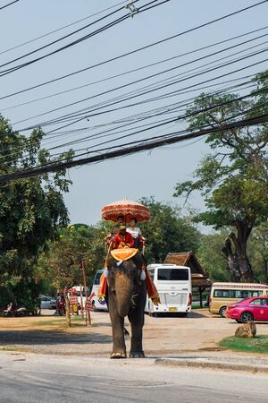 Ayutthaya, Thailand - February 5, 2018: Tourists on an elephant ride tour of the ancient city Ayutthaya in Thailand. Elephant in red blanket with folk patterns carries a tourist to see the sights