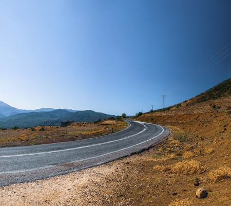 Panoramic landscape with asphalt road and mountains over blue clear sky. Road that leads to the monasteries on the top of Meteora , Greece Banco de Imagens