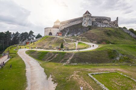 Rasnov, Romania - September 7, 2017: Panoramic view of the inner courtyard of the Rasnov Fortress with walking tourists in the foreground, Rasnov city, Brasov county, Romania