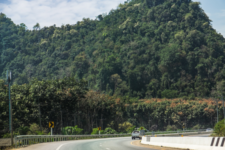 Asphalt road, tropical forest and mountains near Khao Sok National Park, Surat Thani Province, Thailand.