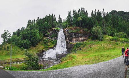 Steine, Norway - August 2, 2018: : Tourists visit and enjoy the view of Steinsdalfossen waterfall in Steine, Norway Editorial