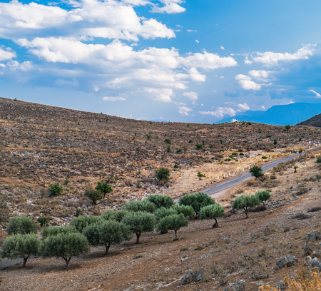Panoramic landscape with asphalt road and mountains over blue cloudy sky in Western Greece Banco de Imagens