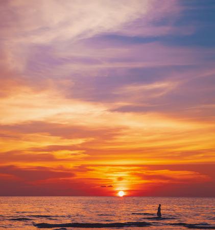 Tropische kleurrijke dramatische zonsondergang met bewolkte hemel. Avondrust aan de Golf van Thailand. Heldere nagloed. Silhouet van zwemmende man op het water Stockfoto