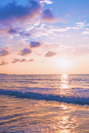 Atardecer de playa tropical pastel con olas y nubes en el cielo azul