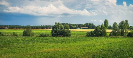 Panorama of typical Finnish countryside in summer in province of Oulu, Northern Ostrobothnia region, Finland. Agricultural fields and wooden houses in village on horizon