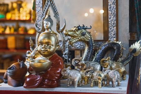 Various Thai Buddha statuettes, silver elephants and dragons and other souvenirs for sale in local Bang Niang Night Market, Khao Lak, Thailand. Stock Photo