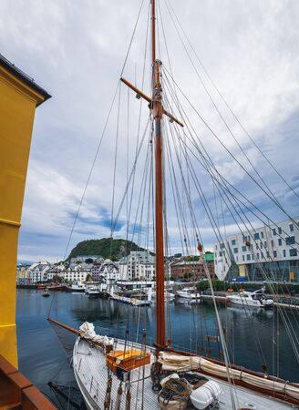 Old Town pier with old boats and sailing ship. Historical district of the Bryggen - Hanseatic wharf in Bergen, Norway. Pier is visible through the tackle boats