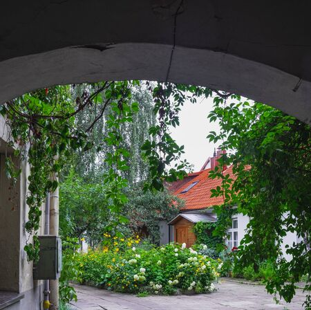 Old courtyard with blooming flower beds a garden with trees near Ausros Vartu pedestrian street in the heart of the Old Town in Vilnius, Lithuania.