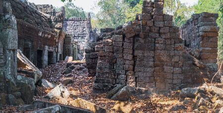 The ancient ruins of the Preah Khan Temple in Siem Reap, Cambodia. A pile of old stones on a tourist road in the foreground. Ancient Khmer architecture, famous Cambodian landmark. Stock Photo