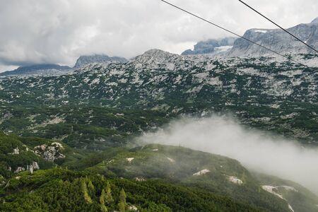 Summer view of Dachstein Mountains in the fog taken from Krippenstein cable car station, Upper Austria, Austria
