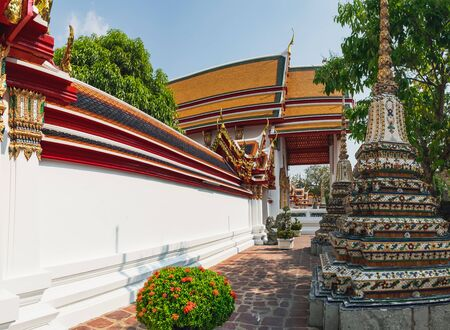 Panorama with ancient stupa and walls of Wat Pho public temple, Bangkok, Thailand. Classical Thai architecture.