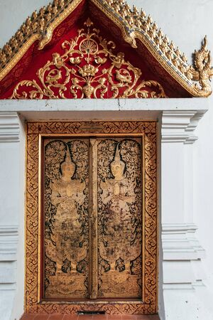 Old yellow-gold pattern with Buddha on the walls of Buddhist temple Wat Phra Singh in Chiang Mai, northern Thailand. Stock Photo