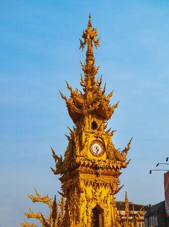 Ornate Golden Clock Tower against blue sky in Chiang Rai, Thailand