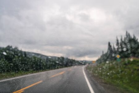 View through the dropped car window to empty road and cloudy natural landscape in Norway. Wet rainy glass, drops on glass, raining concept, motion blur
