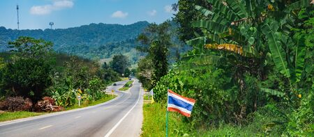 Asphalt road with Thai flags in a row, tropical forest and mountains near Khao Sok National Park, Thailand. It is the main tourist route to the Andaman sea - Phuket Island and Khao Lak. Stock Photo