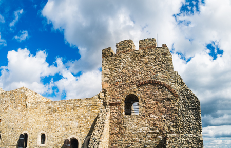 Tower of the Neamt Citadel under the cloudy blue sky. It is a medieval fortress located in north-eastern part of Romania, near Targu Neamt, Neamt County.