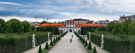 Panoramix view with walking tourists through the beautiful Belvedere garden to Lower Belvedere Palace, Vienna, Austria.