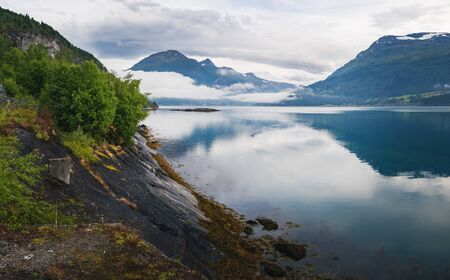 Nordfjord is a bay near Stryn village and district in Sogn og Fjordane, Norway, Norway. Scandinavian nature fjord and mountain in National Park in summer. Summer view of scenic fog over the mountains