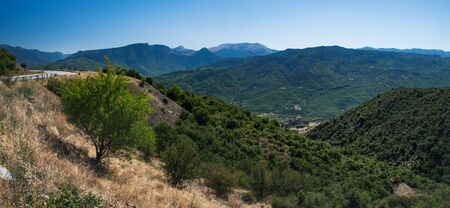 Panoramic landscape with asphalt road and mountains over blue clear sky. Road leads to the monasteries on the top of Meteora , Greece