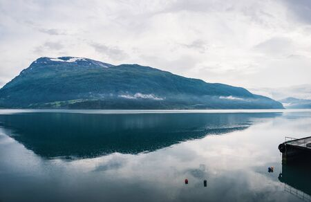 Nordfjord is a bay near Stryn village and district in Sogn og Fjordane, Norway, Norway. Summer rain over the fjord, water surface in raindrops. Scenic view of mountain reflections