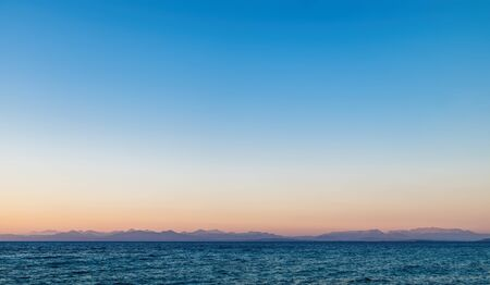 Idyllic sunset on the shore of north west coast of Lefkada island, Greece. Simple seascape with water surface and sunset sky Stock Photo