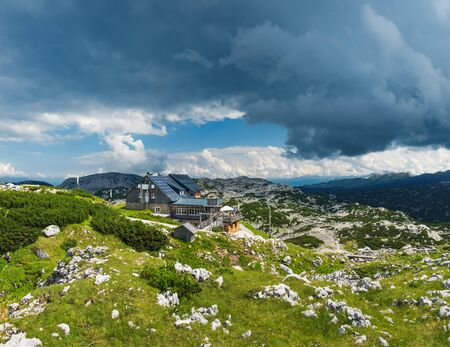 Panoramic summer view of wooden house in the Dachstein Mountains taken near Krippenstein cable car station in Upper Austria, Austria