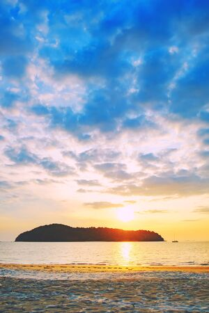 Pantai Tengah Beach at colorful sunset, Langkawi Island, Malaysia. Beach sunset is a golden sunset sky with a wave rolling to shore as the sun sets over the horizon. Banque d'images