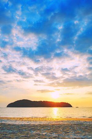Plage de Pantai Tengah au coucher du soleil coloré, île de Langkawi, Malaisie. Le coucher de soleil sur la plage est un ciel doré au coucher du soleil avec une vague qui roule vers le rivage alors que le soleil se couche à l'horizon. Banque d'images