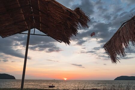 Silhouette of the beach hut with thatched roof on the beach. Tropical colorful dramatic sunset and color parachute in cloudy sky, Pantai Tengah Beach, Langkawi Island, Malaysia.