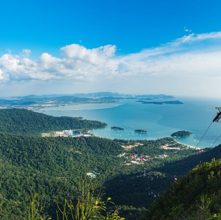 Cable Car to the top of Langkawi island and view of blue sky, sea and mountain, Malaysia, tropical plants in the foreground. Langkawi SkyCab is one of the major attractions in the island