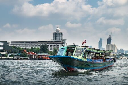 Tourist popular boat travel on the Chao Phraya river, Bangkok, Thailand. River taxi with Thai flag in the foreground and skyscrapers of Chinatown are seen on the horizon