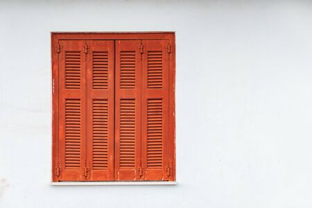 Greek Style windows - wooden vintage window with brown shutters on a white wall. Closed house window, Delphi, Greece