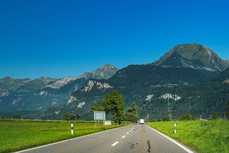 View through the car window to road and natural landscape at foot of Brienzer Rothorn mountain in Bernese Oberland region, Switzerland. Motion blur, selective focus on the center Stock Photo
