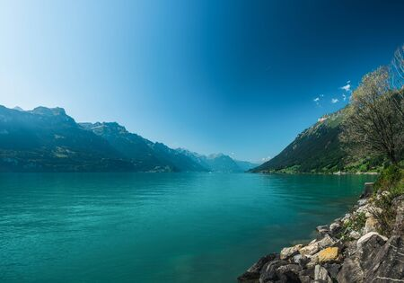 Idyllic sunny day on the Lake Brienz or Brienzersee in Berner Oberland, Canton of Bern, Switzerland. Scenic landscape with picturesque mountains, blue sky and turquoise water of lake Stock Photo