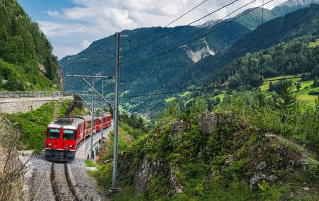 A tourist train traveling on the railway through Sumvitg valley of Switzerland. Banque d'images