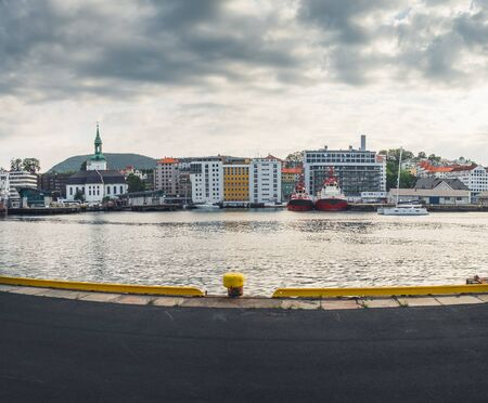 Scenic summer panoramic view of the modern pier architecture, beautiful waters of Byfjorden and cloudy sunset in Bergen, Norway
