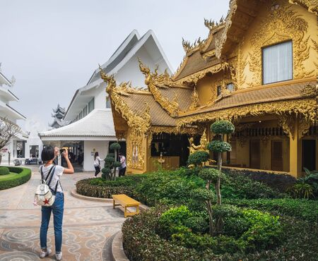 Chiang Rai, Thailand - February 9, 2018: Tourist makes photo of beautiful white and yellow ornate buildings in White Temple - Wat Rong Khun in Chiang Rai, Thailand Zdjęcie Seryjne - 137984712