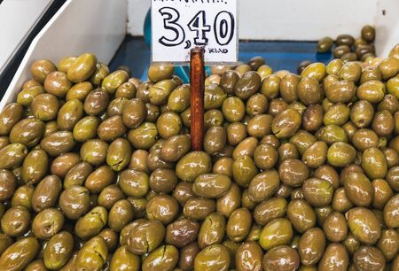 Green olives for sale at the Athens Central Market in Greece. Containers with olives and price tag. Фото со стока