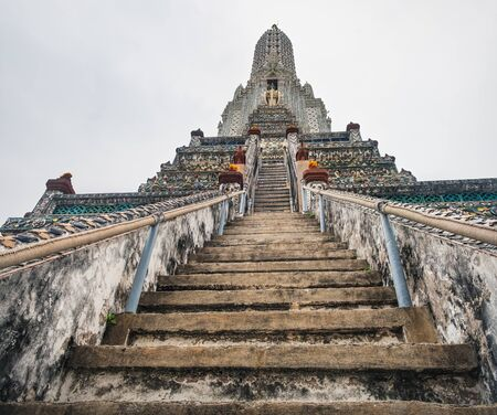 Stairs to the top of Stupa-like pagoda encrusted with coloured faience in Temple of Dawn, Wat Arun, Bangkok, Thailand.