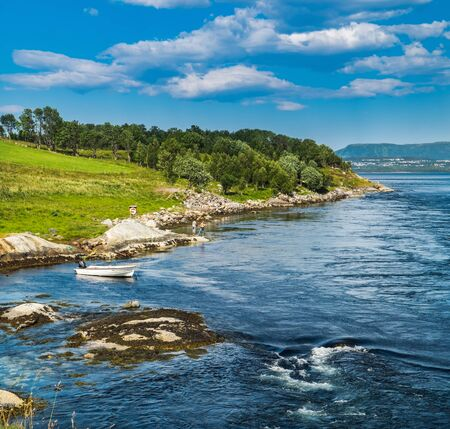 People fishing on rocks next to fjord in Norway. Norwegian fisherman in summer landscape, fisher boat in stream with whirlpools near Saltstraumen bridge, Bodo, Nordland