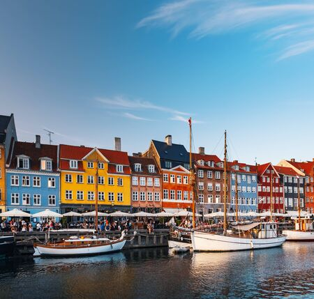 Scenic summer view of canal and Nyhavn pier with colorful buildings, ships, yachts and boats in Old Town of Copenhagen, Denmark. People walking and resting in Copenhagen harbor, scenic summer view Zdjęcie Seryjne
