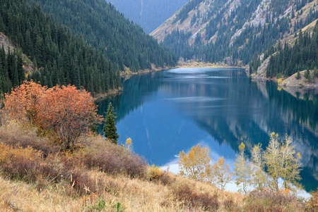 Autumn trees on the coast of the mountain lake Kolsai, Kazakhstan photo