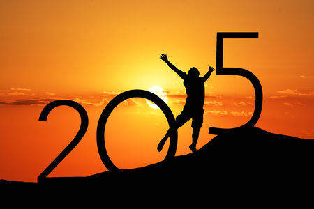 new years resolution: Silhouette person jumping over 2015 on the hill at sunset Stock Photo