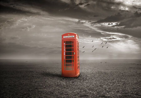 Old-fashioned traditional red telephone booth on deserted field photo
