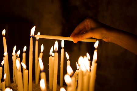 churches: woman hand lighting candles  in a church