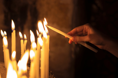 candela: donna illuminazione candele in una chiesa Archivio Fotografico